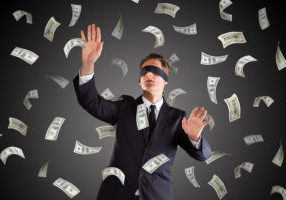 A Blindfolded Lost Businessman Standing Under Money Rain On Gray Background