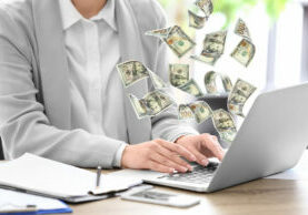Woman With Modern Laptop And Flying Dollar Banknotes At Table In